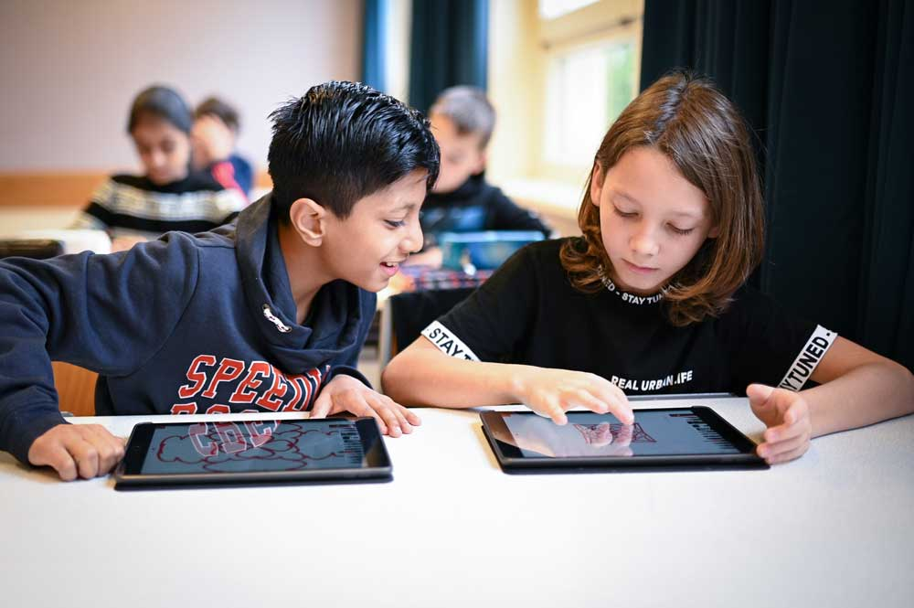 Schüler*innen arbeiten mit iPads im Unterricht