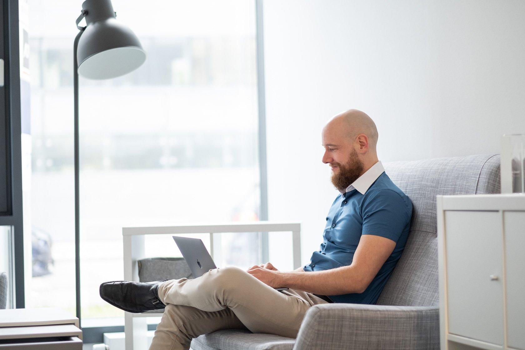 Mann arbeitet am MacBook von zu Hause